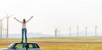 Mulher sobre o carro no campo entre turbinas eólicas. Imagem de Stock