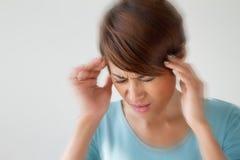 A mulher sofre da dor, dor de cabeça, doença, enxaqueca, esforço