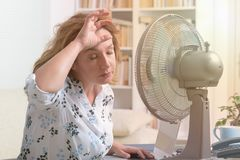 A mulher sofre do calor no escritório ou em casa fotos de stock royalty free