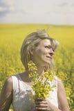 A mulher sonhadora bonita em um campo da colza com um ramalhete sonha e aprecia a natureza imagem de stock
