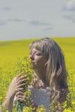 A mulher sonhadora bonita em um campo da colza com um ramalhete sonha e aprecia a natureza fotos de stock
