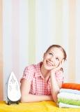 A mulher sonhadora da dona de casa com ferro contratou no trabalho doméstico fotos de stock