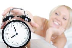 A mulher sonolento desliga o alarme Fotos de Stock Royalty Free