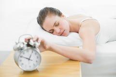 Mulher sonolento na mão de alargamento da cama ao despertador Fotografia de Stock