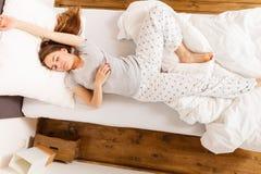 Mulher sonolento que dorme na cama imagem de stock royalty free