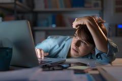 Mulher sonolento que trabalha com seu portátil imagens de stock