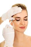 A mulher sorrida nova está tendo a injeção facial do botox imagem de stock