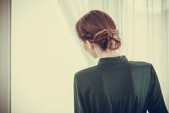 Mulher sozinha que olha com da espera da janela fotos de stock royalty free