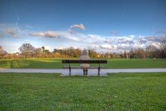 Mulher sozinho no banco de parque Foto de Stock
