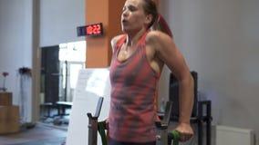 A mulher suado cansado da aptidão que faz mergulhos da barra malha no gym vídeos de arquivo