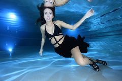 Mulher subaquática com saltos altos imagem de stock