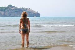 A mulher sujada está estando na costa de mar Foto de Stock