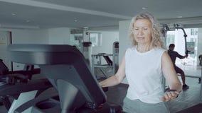 A mulher superior é contratada em uma escada rolante no gym na perspectiva da janela panorâmico filme