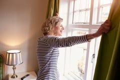 A mulher superior abre cortinas para olhar a vista de uma janela Imagem de Stock