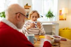 Mulher superior agradável que guarda um copo com chá delicioso foto de stock royalty free