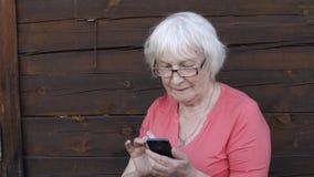 Mulher superior alegre nos vidros usando o telefone esperto exterior video estoque