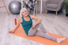 Mulher superior alegre que descansa após a prática da ioga fotos de stock royalty free