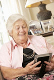 Mulher superior aposentada feliz que senta-se na fotografia de Sofa At Home Looking At Fotografia de Stock Royalty Free