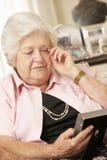 Mulher superior aposentada infeliz que senta-se na fotografia de Sofa At Home Looking At Foto de Stock
