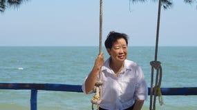 Mulher superior asiática apenas no pensamento do nascer do sol do mar imagens de stock