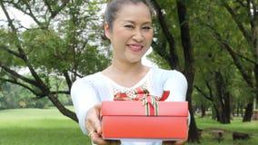 Mulher superior asiática para dar a caixa atual ao operador atrás da câmera Uma mulher dá um presente filme