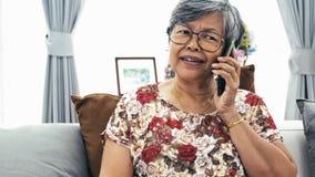Mulher superior asiática que fala com telefone esperto em casa, filme