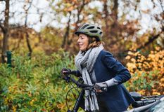 Mulher superior ativa com o electrobike que dá um ciclo fora no parque fotos de stock