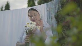 Mulher superior bonita com o xaile branco em seus rasgos principais fora das pétalas da margarida na corda fora washday positivo filme