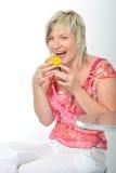 Mulher superior bonita que sorri no macaro amarelo comer cor-de-rosa do terno Imagem de Stock