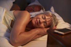 Mulher superior calma adormecida na cama na noite fotografia de stock