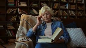 Mulher superior cansado agradável que lê um livro video estoque