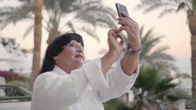 Mulher superior caucasiano de sorriso que faz o selfie no smartphone Deve estar no terraço do hotel em um terry branco video estoque