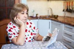Mulher superior caucasiano triste que olha as contas com dinheiro do dinheiro à disposição ao sentar-se na cozinha imagem de stock
