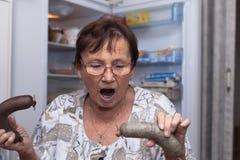 Mulher superior chocada que guarda salsichas de fígado da carne de porco Fotografia de Stock