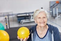 Mulher superior com a bola na terapia ocupacional fotografia de stock