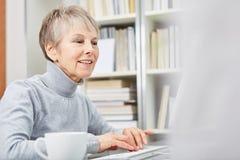 Mulher superior com computador Fotografia de Stock