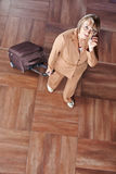 Mulher superior com a mala de viagem que faz o telefonema fotografia de stock