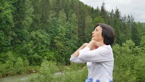 Mulher superior com o cabelo escuro curto que faz um exercício de esticão para o abrandamento na manhã fora sobre a paisagem de video estoque