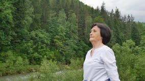 Mulher superior com o cabelo escuro curto que faz um exercício de esticão para o abrandamento na manhã fora sobre a paisagem de vídeos de arquivo