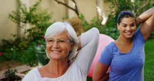 Mulher superior com o instrutor fêmea que faz esticando o exercício no jardim 4k vídeos de arquivo