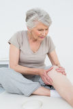 Mulher superior com suas mãos em um joelho doloroso Fotografia de Stock Royalty Free