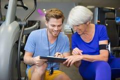 Mulher superior da assistência pessoal do instrutor que exercita na máquina no gym imagem de stock royalty free