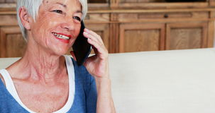 Mulher superior de sorriso que fala no telefone celular na sala de visitas filme