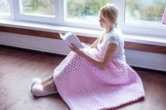 Mulher superior de sorriso que lê um livro em casa fotos de stock royalty free