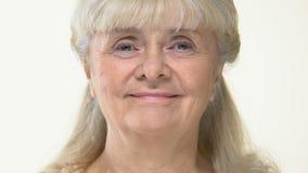 Mulher superior de sorriso que olha a câmera no fundo branco, beleza da idade avançada, harmonia filme