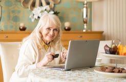A mulher superior de sorriso usa o portátil e o cartão de crédito ao sentar-se na tabela fotos de stock royalty free