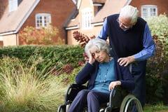 Mulher superior deprimida na cadeira de rodas que está sendo empurrada pelo marido foto de stock royalty free