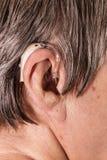 Mulher superior do close up que usa a prótese auditiva Imagens de Stock Royalty Free