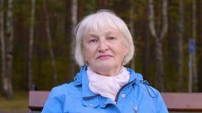 Mulher superior do retrato com cabelo cinzento no banco no parque do outono que olha na câmera video estoque