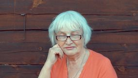 Mulher superior do retrato com o cabelo cinzento que olha in camera no fundo de madeira da parede video estoque